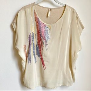 Cream top with detailed colorful stitching